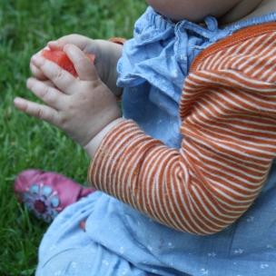 das Landkind muss erst einmal die Melone gründlichst untersuchen, bevor es sich die Leckerei schmecken lässt..