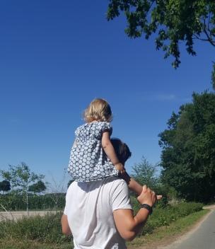 Die Landstraße brennt heiß unter den Füßen, das Landkind lässt sich gern vom Papa tragen..